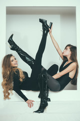 Girls fashionable flexible skinny posing niche wall white background. Ladies black bodysuits tights high heels looks bored. Friends in tight clothes bored invent pleasure. Girls just want to have fun