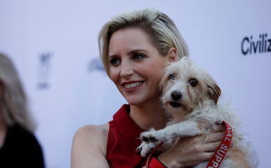 """Director Feste holds her dog Loretta as she poses at the premiere for the movie """"Boundaries"""" in Los Angeles"""