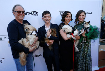 "Cast members Fonda, MacDougall, Schaal and Farmiga hold dogs as they pose at the premiere for the movie ""Boundaries"" in Los Angeles"