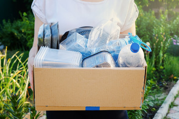 Woman holding a carton with plastic bottles, prepairing for recycling