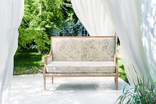 Luxury modern gazebo with soft furniture and curtains inside garden. Summer wedding ceremony pavilion.