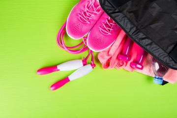 pink clothes and accessories for fitness, a bottle of water, in a sports bag, on a light green background