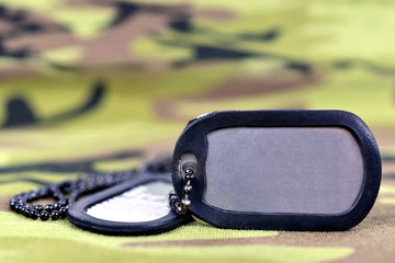 Military dog tags on camouflage fabric.