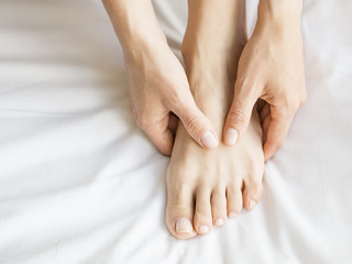Woman Holding her Tired Feet in Hand Sitting on Bed with White Sheets.