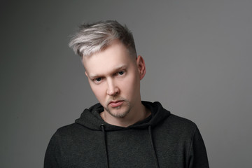 Young man with gray hair in casual clothes on white and gray background. Portrait in the studio. Creative hair coloring.