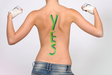 A young semi nude girl has her back turned to the camera. She has the word yes painted in green on her back. She  poses in a muscle show off pose.She wears white gloves  on her hands.