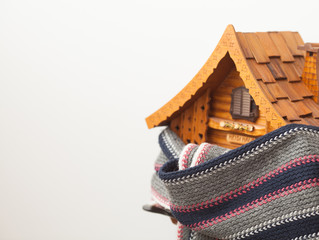 small wooden house in a warm scarf. Home insulation concept.
