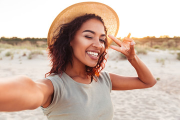 Happy young excited african lady make selfie Wall mural