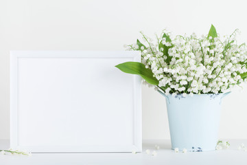 Mockup of picture frame decorated flowers in vase on white background with clean space for text.