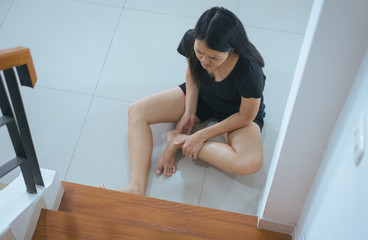 Asian woman falling down of staircase,Hands female touching her legs injured