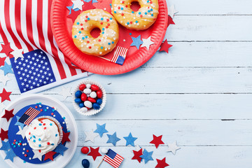 Fourth of July american Independence Day background decorated with USA flag, donut with candys, stars and confetti.
