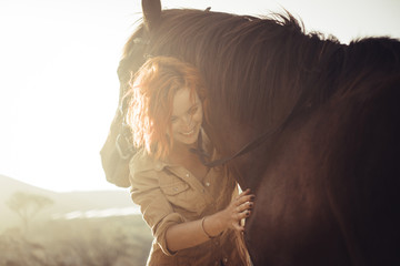 real love and friendship concept between nice beautiful caucasian lady and amazing horse. sunset time and backlight. sweetness and tenderness in horses therapy.