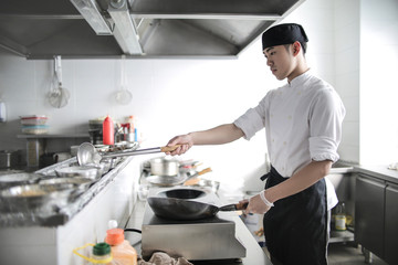 Chinese chef cooking in a restaurant kitchen