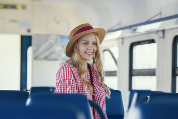Young caucasian woman in hat with wavy hair smiling in speed train