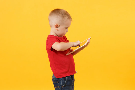 Little cute kid baby boy 3-4 years old in red t-shirt holding in hand tablet pc computer isolated on yellow background. Kids childhood lifestyle concept. Problem of children and gadgets. Copy space.