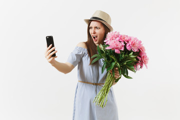 Irritated dissatisfied woman holding bouquet of beautiful pink peonies flowers, doing selfie on mobile phone isolated on white background. St. Valentine's, International Women's Day holiday concept.