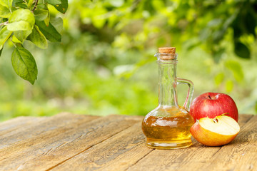 Apple vinegar in glass bottle and fresh red apples on wooden boards with green natural background