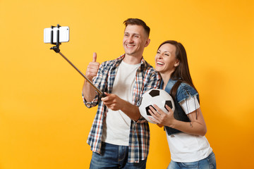 Young couple, woman man, football fans doing selfie on mobile phone with monopod selfish stick, cheer up support team, soccer ball isolated on yellow background. Sport family leisure lifestyle concept