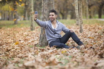 Handsome man in nature taking selfie pictures with his smartphone. Autumn. Copy space