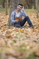 Handsome man in nature holding autumn leaves. Copy space