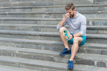 In de dag Ontspanning Tired after training on fresh air. Stay hydrated and healthy. Macho with water bottle sit on steps, copy space. Thirst. Strong man with plastic flask relax on stairs. Sport and fitness