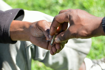 Two black hands of South African male smokers exchanging cigarette outdoors on a sunny day.