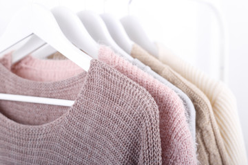 Wall Mural - Warm knitted, autumn, winter clothes hanging on a rack, trending concept,pastel colors