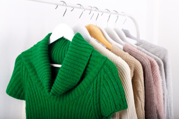Wall Mural - Warm knitted, autumn, winter clothes hanging on a rack, trending concept