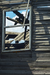 Fragment of the destroyed burned wooden house wall and window. Remains of the structure. View through the window