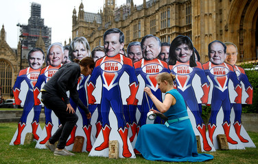 Anti-Brexit campaigners from global activism group Avaaz, pose cardboard cut-outs of Conservative Party MPs, who are know to support remaining in the EU, outside parliament in Westmionster London