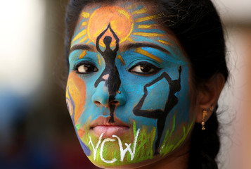 A college student poses as she displays her painted face as an awareness ahead of International Yoga Day, in Chennai