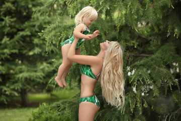 Summer family vacation. Fashion look blond girls portrait. Beautiful Mother throws up her little daughter, wears in  green swimwear having fun at park.