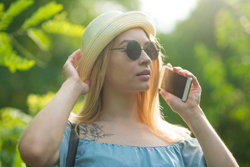 Human facial expressions and emotions. Fashionable young woman in stylish sunglasses with a nice telephone conversation, smiling, relaxing in the city park