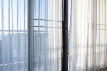 The sunlight shining through the curtain into the bedroom