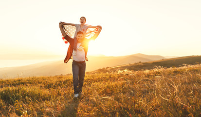 happy family father and child  with flag of united states enjoying  sunset on nature.