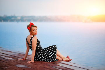 A beautiful young woman dressed sitting on the pier