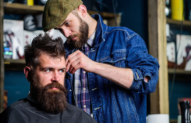 Barber in denim jacket busy with trimming hipster, barbershop background. Client with beard and mustache covered with cape. Barber work on haircut with hair clipper equipment. Image making concept