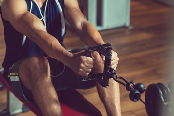 Close-up shot of young muscular man doing exercise on rowing machine at modern gym while having intensive workout