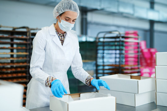 Confectioner in white coat preparing empty paper box at factory.