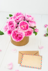 Tender pink tea roses bouquet in vintage pot, blank of greeting card and craft paper envelope on white wooden background. Postcard mock up. Summer, spring flowers. Selective focus. Copy space.