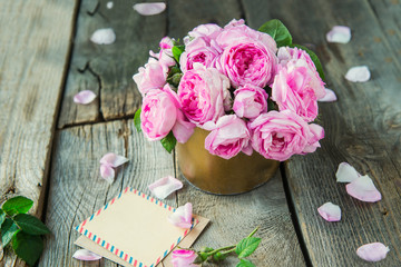 Tender pink tea roses bouquet in vintage pot and blank of greeting card on rustic old wooden table. Floral background. Postcard mock up. Summer, spring flowers. Selective focus. Copy space.