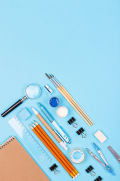 Stationary on blue background. Notebook, pencils, ruler, paints, brushes and other. Knolling concept.