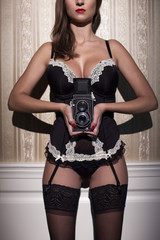 Sexy woman in underwear holding film camera at vintage wall