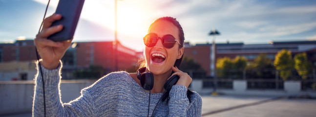 Excited young woman laughing during video chat outdoors banner