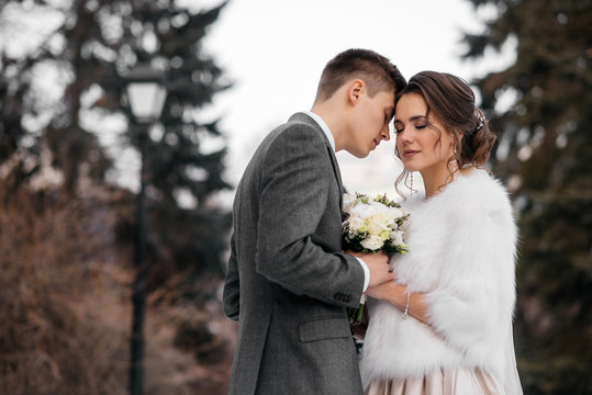 Loving and beautiful bride and groom stand in an embrace in the winter forest