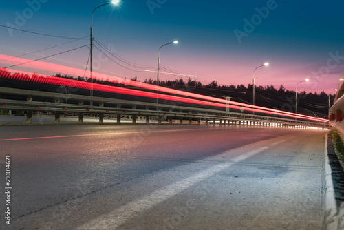 The car light trails on the road with metal safety barrier