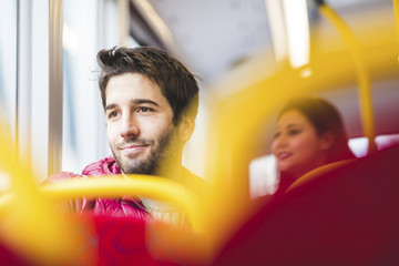 UK, London, portrait of smiling young man in bus looking out of window