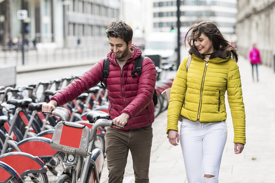 UK, London, young couple with rental bicycle from bike share stand