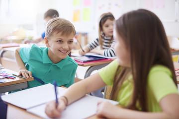 Schoolboy smiling at schoolgirl in class