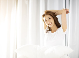 young Woman stretching in bed after wake up